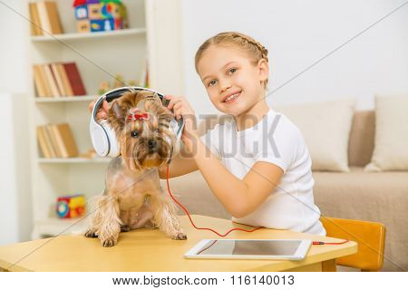Little girl putting headphones on the dog.