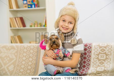 Little girl and her pet dressed in warm clothes.