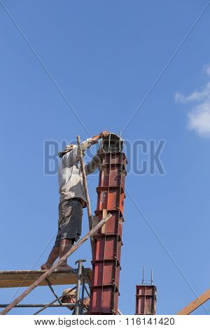 Worker Pouring Cement To Concrete Pillar Mold For House Construction