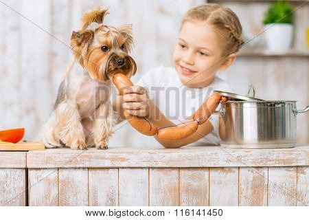 Little girl is feeding sausages to her dog.
