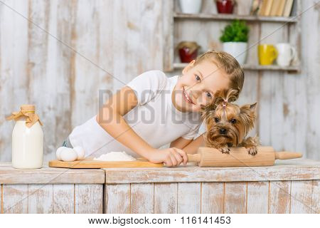 Little smiling girl is leaning down to her pet.