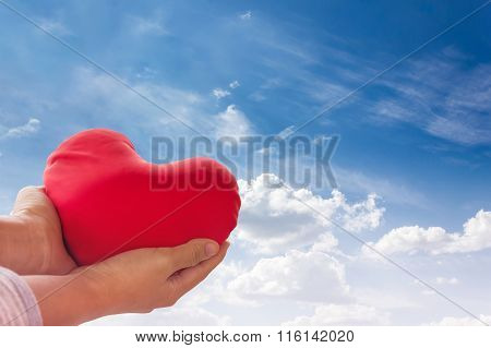 Romantic Lovely Valentine Concept With Hand Gently Raise Up Red Heart On Blue Sky Background