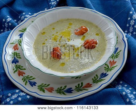 broccoli cream soup with baked cherry tomatoes, cream and parmesan  cheese