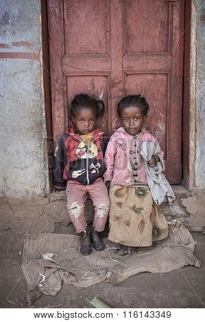 OROMIA, ETHIOPIA-NOVEMBER 4, 2014: Unidentified children sit in a doorway in Ethiopia wearing donated clothing.