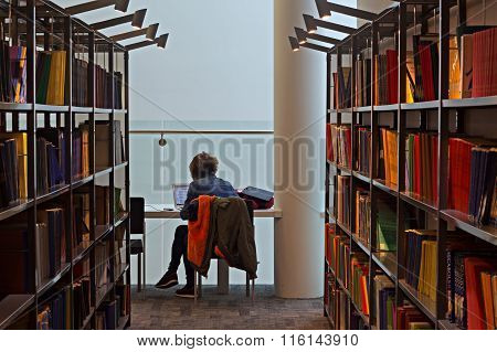LIVERPOOL UK 16TH JAN 2016. Blurred Books And Student Studying In A Library