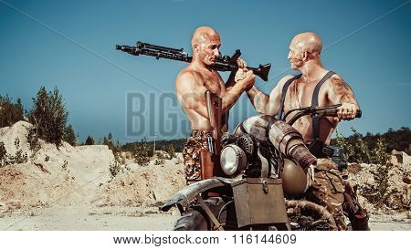 Two Powerful Bald Bikers With Guns On The Desert Background.