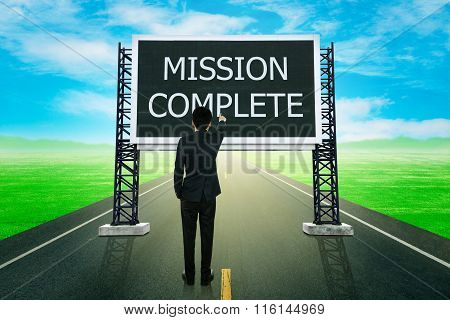Businessman Standing On Road And Pointing With Large Sign Of Mission Complete