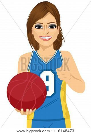 female basketball player holding ball and showing thumbs up