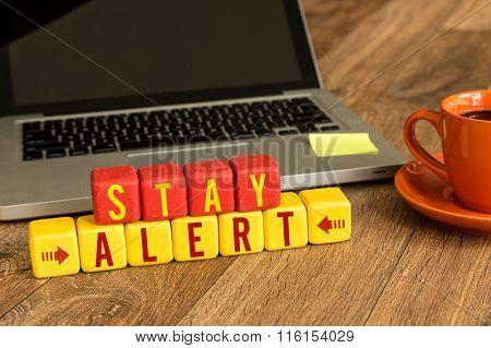 Stay Alert written on a wooden cube in a office desk