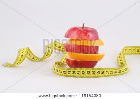 Apple And Orange Slices Combined By A Pyramid And A Measuring Tape On A White Background