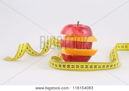 Red Delicious And An Orange Slices On A White Background And A Measuring Tape