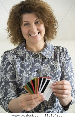 woman holding a credit card and thinking about buying