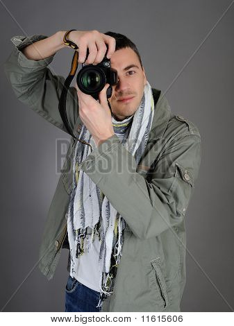Professional Male Photographer Taking Picture . Isolated On Gray Background