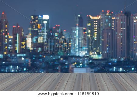Opening wooden floor, Blurred bokeh light city downtown aerial view.