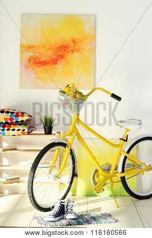 Yellow bicycle with sneakers in light living room interior