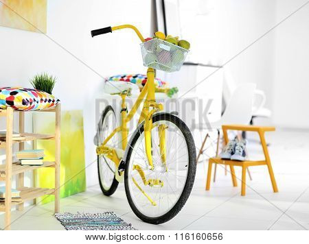Yellow bicycle in light living room interior