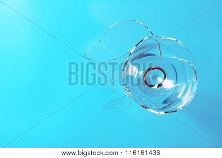 Broken wine glass on blue background