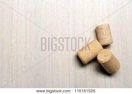 Three wine corks on light wooden background