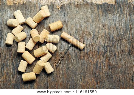 Wine corks and corkscrew on old wooden background