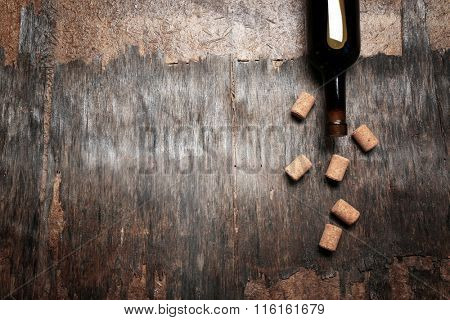 Wine corks and bottle on old wooden background