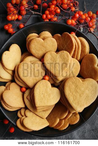 Heart shaped biscuits with ash berries on a mat, top view
