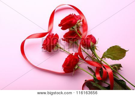 Red Roses And Ribbon On Pink Background