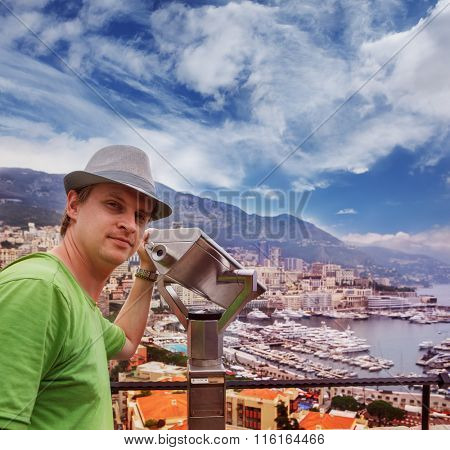 Tourist in Monaco looking at the Port Hercules area with yachts