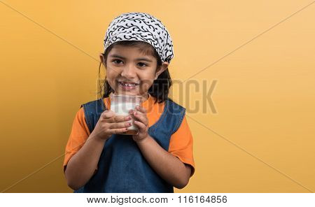 4 year old indian girl with a glass full of plain white milk, indian girl and plain milk, indian gir