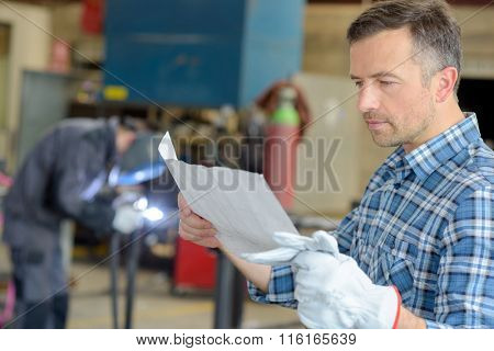 man looking at a paper
