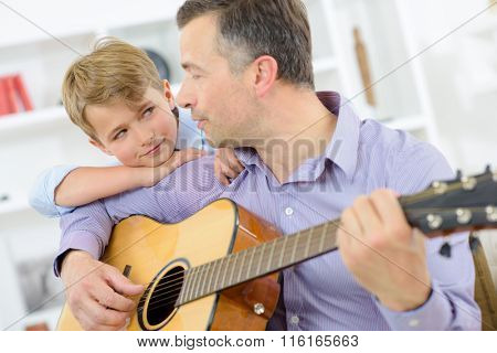 Man playing guitar, child leaning on his shoulder