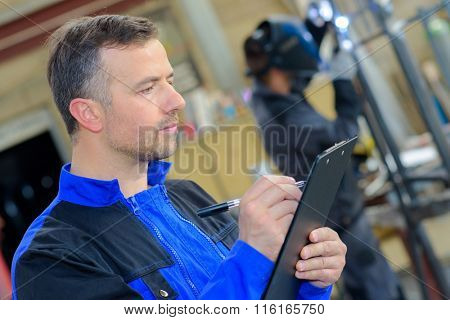 Workman making notes on clipboard