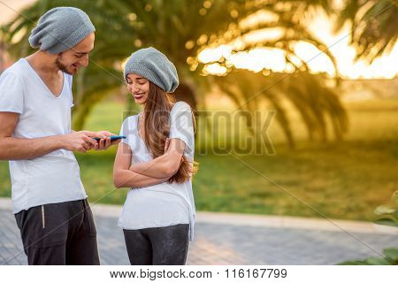 Couple using phone in the park