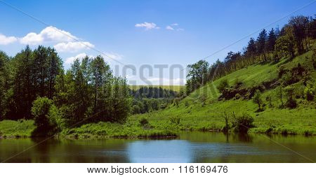 Landscape Of A River, Green Grassy Hills With Trees And Sky