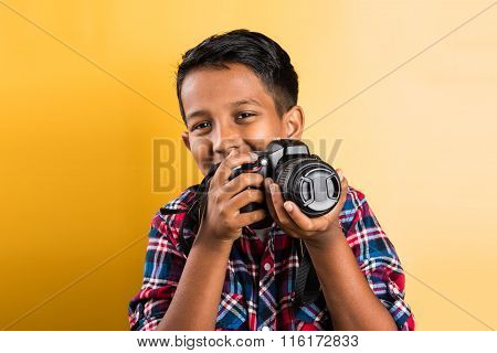 10 year old indian boy holding digital camera or DSLR camera, posing like a professional photographe