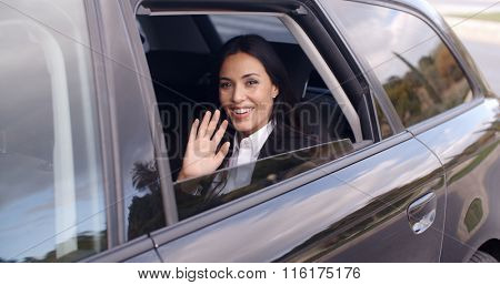 Cute business woman sitting in car waving hand