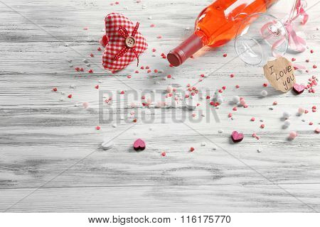 Love concept - wine bottle with decorations on white wooden background, close up