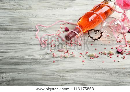 Love concept - wine bottle with decorations on white wooden background
