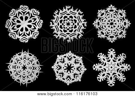 Snowflakes cut out of paper on a black background