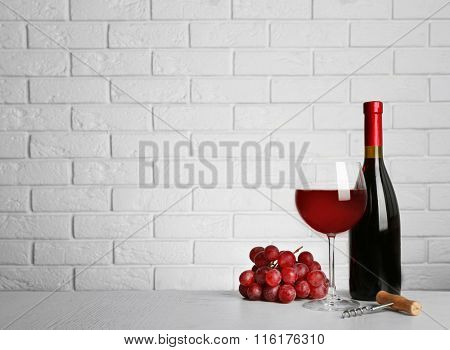 Red wine and grape on brick wall background