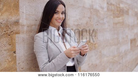 Female worker texting and leaning against wall