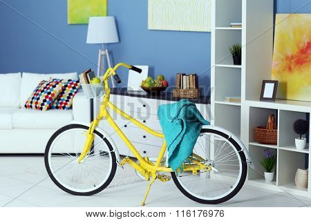 Yellow bicycle with blue cover in light living room interior