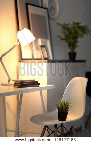 Room interior with commode with chair, plant, frames and clock on white wall background