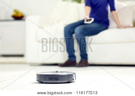 Robotic vacuum cleaner cleaning the room while woman sitting on sofa, closeup