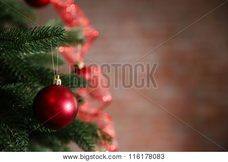 Christmas tree with decor on dark brown background, closeup