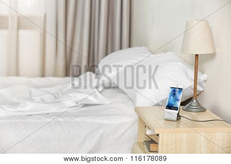 Smart phone on nightstand in bedroom