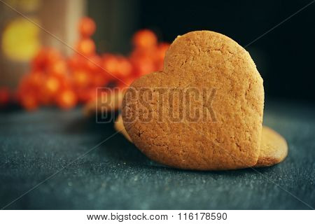 Heart shaped biscuits with ash berries on a table