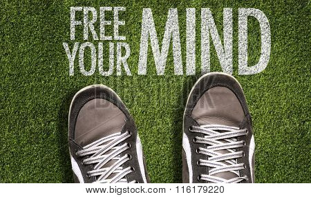 Top View of Sneakers on the grass with the text: Free Your Mind