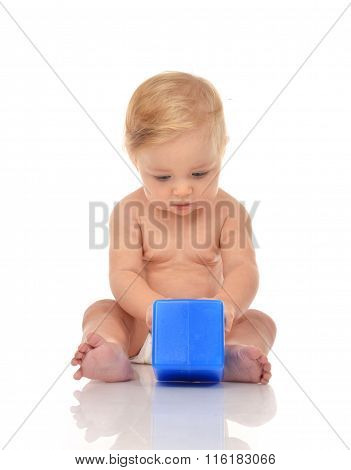 Cute Infant Child Baby Girl Toddler Sitting With Blue Toy Brick In Hand