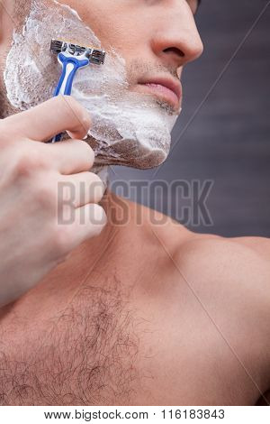 Cheerful young guy shaves his stubble
