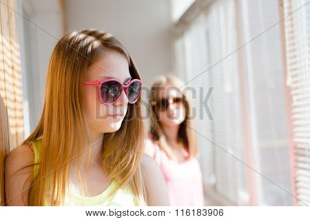 Two beautiful blond teenage girls standing in distance upset